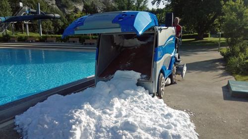 Diese Badi in Chur tut alles für ihre hitzegeplagten Gäste - und karrt mitten im Sommer einen Haufen Schnee neben das Becken. (Bild: Facebook / Obere Au Bäder & Sportanlagen)