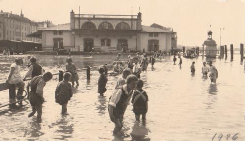 Kinder waten durch das Hochwasser (1926).