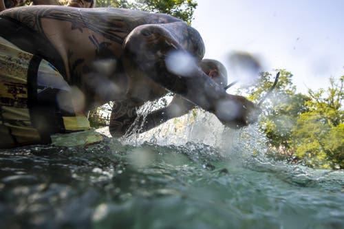 Ein Mann erfrischt sich in der Aare. (Bild: Anthony Anex / Keystone)