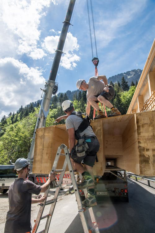 Arbeiter hängen die Holzkonstruktion an das Seil des Pneukrans. (Bild: Nadia Schärli, 3. Juni 2019)