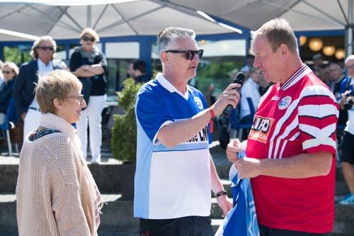 Jürgen Mohr übergibt sein FCL-Retroleibchen einer Anhängerin, die es bei der Verlosung gewonnen hat. In der Mitte moderiert Stefan «Büsché» Bucher. (Bild: Eveline Beerkircher-Bachmann (Sempach, 8. Juni 2019))