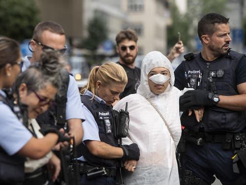 Polizisten führen am Montag Klimaaktivisten ab vor dem Eingang der Credit Suisse auf dem Paradeplatz in Zürich. (Bild: KEYSTONE/ENNIO LEANZA)