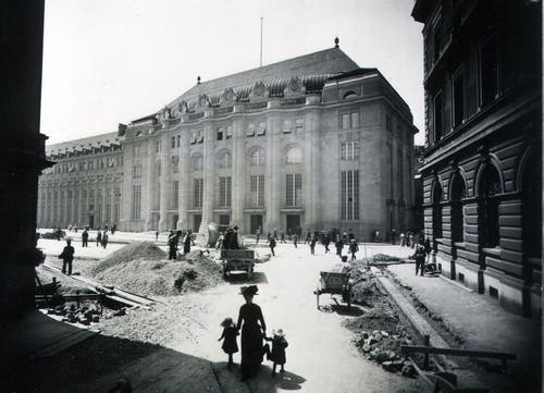Der St.Galler Bahnhofplatz zwischen 1913 und 1915. Die Frau mit Kinde befindet sich auf der Zollhausstrasse, die heute nicht mehr existiert. Rechts ist die ehemalige Hauptpost zu erkennen, die bereits als Rathaus dient und 1977 abgebrochen wurde. Dadurch entstand der heutige Kornhausplatz.