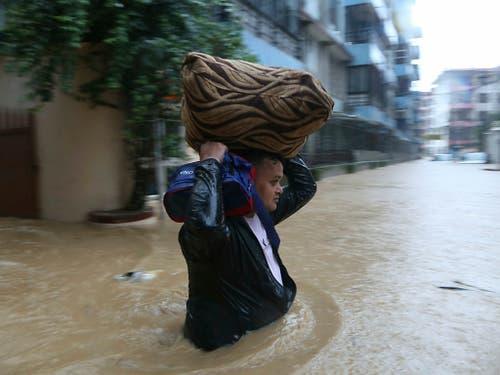 Ein Nepalese kämpft sich durch eine überflutete Strasse in der Hauptstadt Kathmandu. (Bild: KEYSTONE/AP/NIRANJAN SHRESTHA)