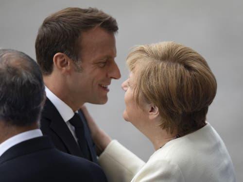 Der französische Präsident Emanuel Macron begrüsst die deutsche Bundeskanzlerin Angela Merkel vor der Parade. (Bild: Keystone/EPA/IAN LANGSDON)