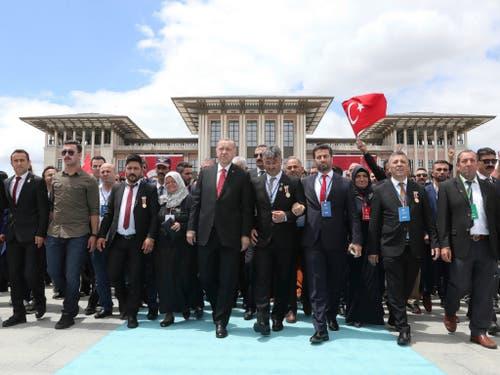 Der türkische Präsident Recep Tayyip Erdogan und Familienmitglieder von Opfern des Putsches marschieren zum Märtyrer-Museum in Ankara. (Bild: KEYSTONE/AP Pool Presidential Press Service)