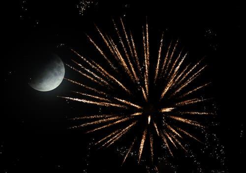 Die partielle Mondfinsternis aufgenommen zusammen mit einem Feuerwerk in Speyer, Deutschland. (Bild: Ronald Wittek)