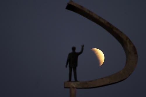 Die partielle Mondfinsternis aufgenommen neben der Statue des früheren brasilianischen Präsidenten Juscelino Kubitschek in Brasilia. (Bild: Eraldo Peres)
