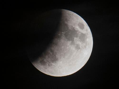Die partielle Mondfinsternis aufgenommen über den Dächern Zürichs. (Bild: KEYSTONE/Ennio Leanza)
