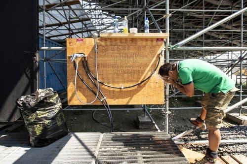 Wasser sorgt für Abkühlung bei den Arbeitern. (Bild: Alexandra Wey / Keystone, 24. Juli 2019)