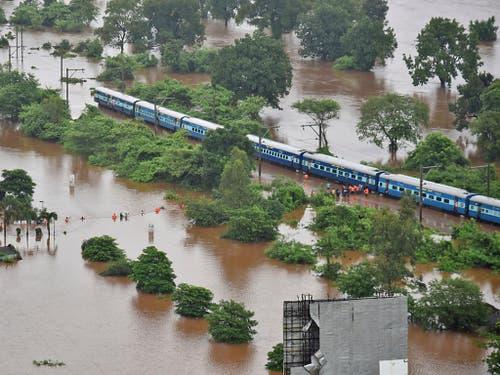 Wegen Hochwassers blieb ihr Zug stecken. Nach stundenlangem Warten wurden 800 Passagiere eines Schnellzugs in Indien von der Marine in Sicherheit gebracht. (Bild: KEYSTONE/AP Indian Navy)