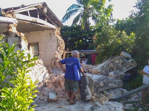 Bewohner vor den Trümmern ihres Hauses nach einer Erdbebenserie im Norden der Philippinen. (Bild: KEYSTONE/AP/AGNES SALENGUA NICO)