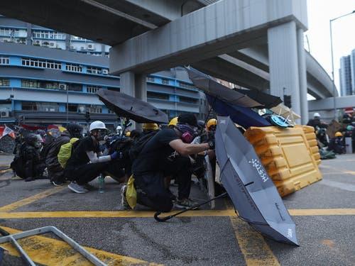 Demonstrierende in Hongkong schützen sich mit Regenschirmen. (Bild: KEYSTONE/EPA/JEROME FAVRE)