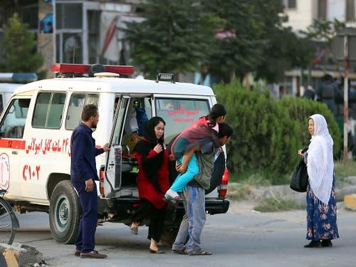 Ein Mann trägt ein verletztes Mädchen. bei den Angriff auf das Büro eines Kandidaten in Kabul ist mindestens ein Mensch getötet worden. (Bild: KEYSTONE/EPA/JAWAD JALALI)