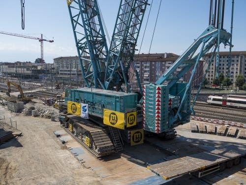 Ein Blick auf den Sockel des Krans und den Zug im Hintergrund verdeutlicht die gewaltigen Ausmasse der Maschine. (Bild: Keystone/JEAN-CHRISTOPHE BOTT)