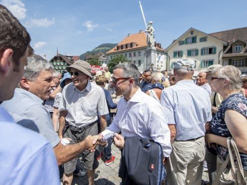 Bundesrat Ignazio Cassis (Mitte vorne) beim Händeschütteln am Apéro mit der Bevölkerung des Kantons Nidwalden. (Bild: Keystone/URS FLUEELER)