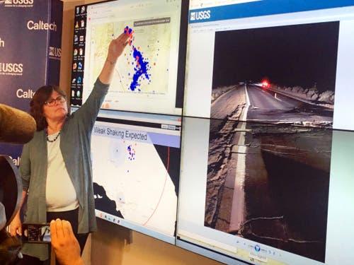 Die Seismologin Lucy Jones von der US-Erdbebbenwarte zeigt eine Übersicht des Erdbebens vom Donnerstag und der darauffolgenden Nachbeben. Rechts das Bild eines Risses in einer Strasse nach dem starken Beben vom Freitag. (Bild: KEYSTONE/AP/JOHN ANTCZAK)