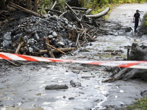 Der Fluss Losentze war am Sonntagabend bei Chamoson VS über die Ufer getreten und hatte ein Auto fortgeschwemmt. Ein 37-jähriger Genfer und ein sechsjähriges Mädchen werden seither vermisst. Die Sucharbeiten sind weiter im Gange. (Bild: Keystone/JEAN-CHRISTOPHE BOTT)
