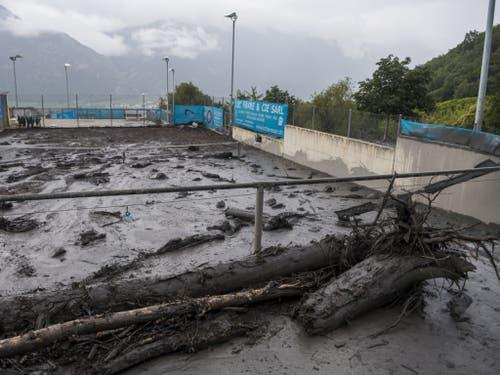 Auch ein Tennisplatz wurde mit Schutt und Geröll überschwemmt. (Bild: Keystone/JEAN-CHRISTOPHE BOTT)