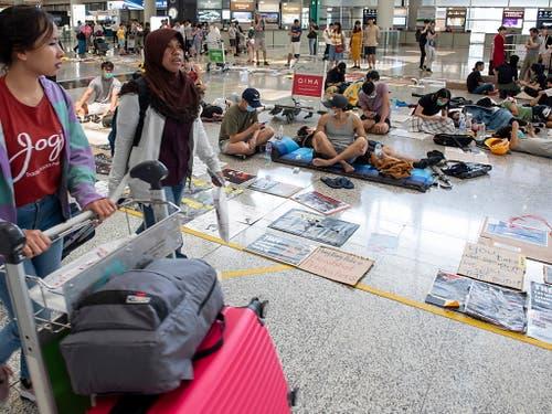Passagiere gehen am Flughafen von Hongkong an Protestierenden vorbei. (Bild: KEYSTONE/EPA/MIGUEL CANDELA)