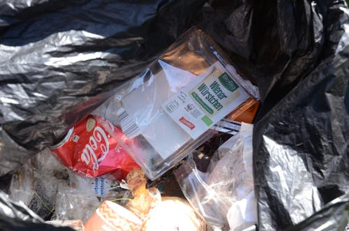 Die Ausbeute von 22 Minuten Müll sammeln: ein Plastiksack voller Müll. Besonders sinnlos erscheinen gewisse Fundstücke: Jemand achtete beim Kauf dieser Wiener Würstchen darauf, dass sie Bio sind und auch andere Labels auf der Verpackung drücken die Nachhaltigkeit für den Planeten aus. Wenn aber dieses Produkt in Plastik verpackt wird und diese Verpackung wiederum im Wald landet, steht es schlecht um die Ökobilanz des Produktes. (Bild: Jessica Nigg)