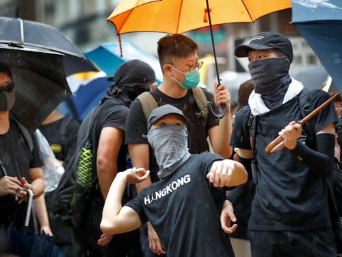 Ein Protestierender bereitet sich auf einen Eierwurf vor. Am Freitagabend und am Samstag sind in Hongkong wiederum Zehntausende auf die Strasse gegangen. (Bild: KEYSTONE/AP/VINCENT THIAN)