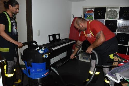 Feuerwehrleute pumpen Wasser aus einem Klavier. (Bild: Thomas Schwizer)