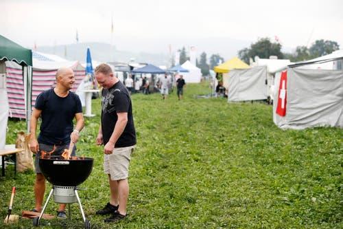 (V.l.n.r.) Walter Mazzini und Mario Moham aus Wartau SG heizen schon mal den Grill an. (Bild: Stefan Kaiser)