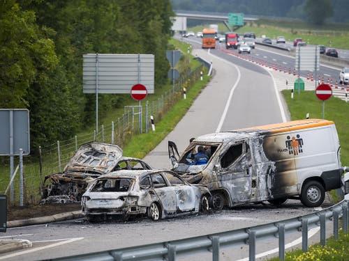 Drei Fahrzeuge brannten nach dem Überfall auf einen Geldtransporter auf der Ausfahrt der Autobahn A1 bei La Sarraz aus. (Bild: KEYSTONE/JEAN-CHRISTOPHE BOTT)