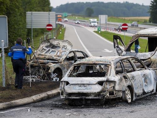 Die Polizei untersucht am Ort des Überfalls die drei verbrannten Fahrzeuge. (Bild: KEYSTONE/JEAN-CHRISTOPHE BOTT)