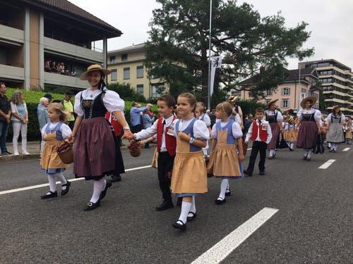 Zuger Trachtenkinder mit Chriesi-Chrättli.