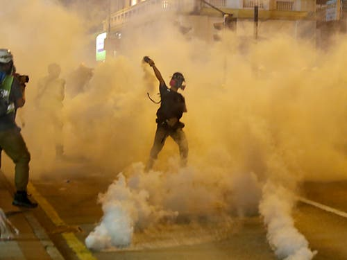 Ein Demonstrant in Hongkong wirft einen Tränengaskanister zurück. (Bild: KEYSTONE/AP/VINCENT THIAN)