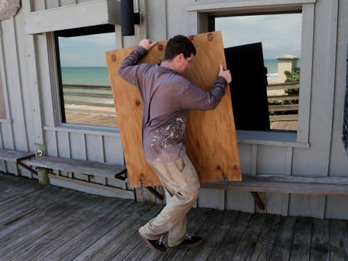 In Vero Beach in Florida macht ein Mann sein Grilllokal möglichst sturmfest. (Bild: KEYSTONE/AP/LYNNE SLADKY)