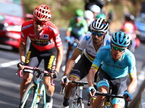 Primoz Roglic (links im roten Trikot) sitzt an der Vuelta weiterhin fest im Sattel. Auch in der 18. Etappe behauptete er seine Führung in der Gesamtwertung gegenüber seinen Konkurrenten - im Bild Weltmeister Alejandro Valverde aus Spanien und Miguel Angel Lopez aus Kolumbien. (Bild: KEYSTONE/EPA EFE/JAVIER LIZON)