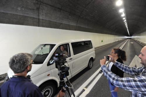 Marcel Giger aus Amden fährt als Erster durch Strasse und wird sogleich von Medienleuten umgarnt. (Bild: Urs Hanhart, Sisikon, 13. September 2019)
