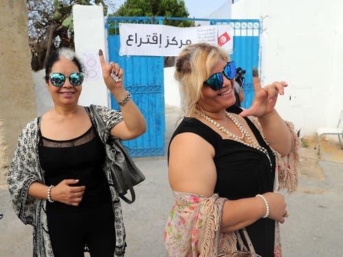 Zwei Frauen vor einem Wahllokal in Tunis mit tintengefärbtem Zeigefinger - der Beleg, dass sie an den Präsidentenwahlen teilnahmen. (Bild: KEYSTONE/EPA/MOHAMED MESSARA)