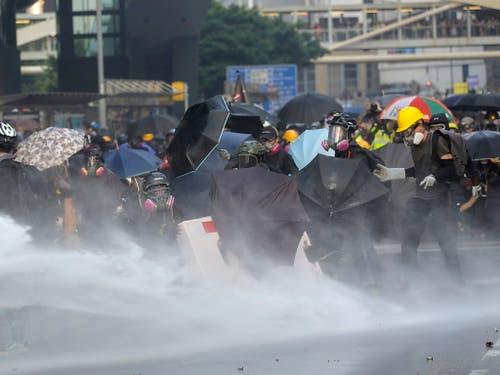Demonstranten schützen sich mit Schirmen vor den Wasserkanonen. (Bild: KEYSTONE/EPA/VIVEK PRAKASH)