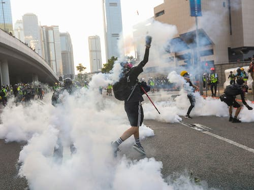 Vor dem Regierungssitz kam es dann zu Zwischenfällen. Demonstranten werfen Tränengas-Kanister der Polizei zurück. (Bild: KEYSTONE/EPA/VIVEK PRAKASH)