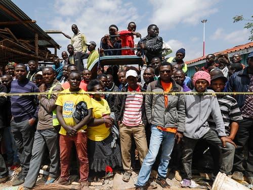 Anwohner und Eltern der Schulkinder beobachten die Aufräumarbeiten nach dem Einsturz einer Schule in Nairobi. (Bild: KEYSTONE/EPA/DAI KUROKAWA)