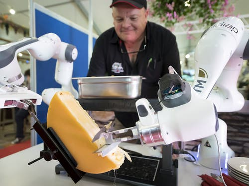 Ein Roboter streicht eine Portion Raclette auf einen Teller. Das Gerät wurde am Samstag an einer Messe in Martigny VS vorgestellt. (Bild: KEYSTONE/LAURENT GILLIERON)