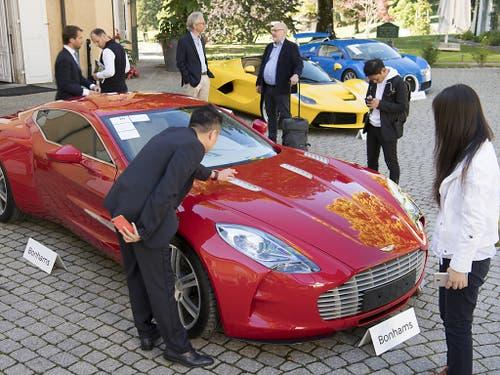Ob das Kleingeld reicht für diesen roten Aston Martin One-77 Coupé aus dem Jahr 2011? Dahinter ein gelber LaFerrari-Ferrari und ein blauer Bugatti Veyron. (Bild: KEYSTONE/LAURENT GILLIERON)