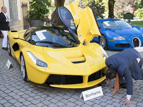 Ein gelber Ferrari LaFerrari von 2015 und ein blauer Bugatti Veyron EB 16.4 Coupé von 2010 ausgestellt an der Versteigerung im Bonmont Abbey Golf & Country Club in Chéserex VD bei Genf. (Bild: KEYSTONE/LAURENT GILLIERON)