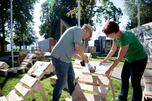 Die beiden OK-Mitglieder Barbara Friedli und Benedikt Felder beschriften die Liegestühle in Sempach. (Bild: Corinne Glanzmann, Sempach, 4. September 2019)