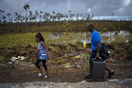 Fernley Cooper und seine Tochter Grace, laufen auf einer zerstörten Strasse. (Bild: AP Photo / Ramon Espinosa)